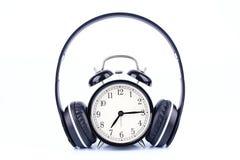 Schwarzer Wecker mit dem Kopfhörer lokalisiert auf weißem Hintergrund Stockfotografie