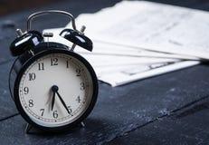 Schwarzer Wecker mit Zeitung auf einem Holztisch Lizenzfreie Stockbilder