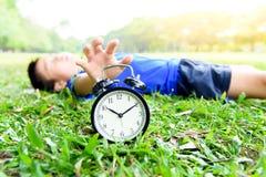 Schwarzer Wecker und schlafender Junge im Park stockbild