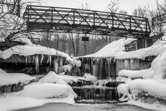 Schwarzer weißer eisiger Wasserfall unter Brücke Stockfotos