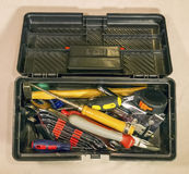 Schwarzer Werkzeugkasten mit dem Haushalt auf hellem Hintergrund lizenzfreie stockbilder