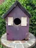 Schwarzes überdachte Vogelhaus mit Fensterläden Stockbild