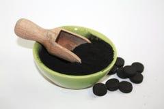 Schwarzes Aktivkohlepulver in einer Schüssel mit hölzernem Gerät und wenigen Pillen als Nächstes stockfoto