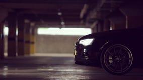 Schwarzes Audi lässt den Parkplatz mit seinen Lichtern stock footage
