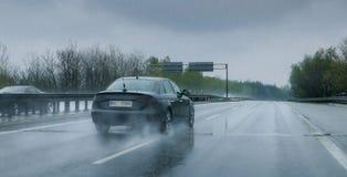 Schwarzes Auto, das durch starken Regen auf Landstraße reist lizenzfreies stockbild