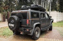 Schwarzes Auto Hummers H2 steht auf ländlichem Parken Stockfotografie