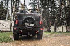 Schwarzes Auto Hummers H2 steht auf ländlichem Parkplatz Stockfotografie