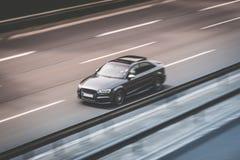 Schwarzes Autoauf Landstraßenstraße, Bewegungsunschärfe schnell fahren Stockfotografie