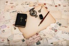 Schwarzes Bibelbuch mit alten Postkarten und Papieren Stockbild