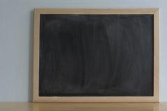 Schwarzes Brett mit Kreide rieb heraus auf hölzerner Tabelle Unbelegtes Feld Stockfoto