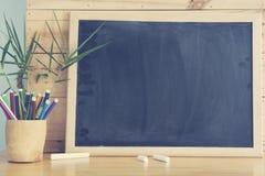 Schwarzes Brett und Stapel des Stiftes auf Holztisch Stockbilder