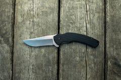 Schwarzes faltendes Messer, das auf alten hölzernen Platten liegt Stockbilder