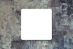 Schwarzes faltete das Weißbuchplakat, das an der schwarzen Steinwand hängt lizenzfreie stockfotos