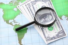 Schwarzes Feld und Bargeld des Vergrößerungsglases auf Welt Lizenzfreies Stockfoto