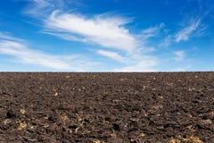 Schwarzes Feld und blauer Himmel Stockfotos