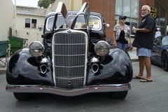Schwarzes Ford 1935 (Vorderansicht) und seine Inhaber Lizenzfreies Stockfoto