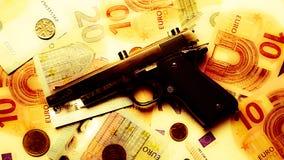 Schwarzes Gewehr, das auf Euroanmerkungen in einem gelben Dunst legt stockbild