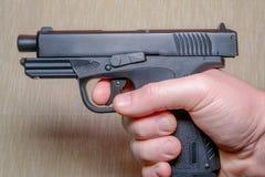 Schwarzes Gewehr im man& x27; s-Hand auf hellfarbigem Hintergrund lizenzfreies stockbild