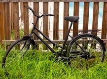 Schwarzes grunge Fahrrad alterte auf einem hölzernen Zaun lizenzfreie stockfotos