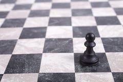 Schwarzes hölzernes Pfand auf Schachbrett Lizenzfreie Stockbilder