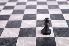 Schwarzes hölzernes Pfand auf Schachbrett Stockbild