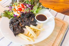 Schwarzes Hühnersteak auf Tabelle lizenzfreies stockbild