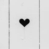 Schwarzes Herz formte Loch in der weißen hölzernen Wand Stockfoto