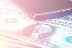 Schwarzes intelligentes Telefon auf US-Dollar Banknotenhintergrund Stockbilder