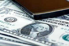 Schwarzes intelligentes Telefon auf US-Dollar Banknotenhintergrund Stockfoto