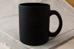 Schwarzes Kaffeetassemodell auf der Leinenserviette stockbild