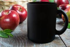 Schwarzes Kaffeetassemodell mit Äpfeln lizenzfreie stockfotos