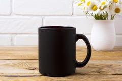 Schwarzes Kaffeetassemodell mit Kamillenblumenstrauß im rustikalen Vase stockbilder