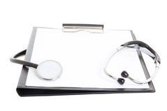 Schwarzes Klemmbrett mit dem Blatt und Stethoskop des leeren Papiers lokalisiert Stockfoto