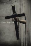 Schwarzes Kreuz mit einer geschlungenen Kette Stockfotos