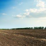 Schwarzes landwirtschaftliches Feld und blauer Himmel Lizenzfreie Stockfotografie