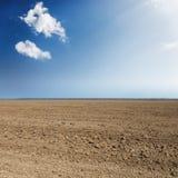 Schwarzes Landwirtschaftsfeld und blauer Himmel mit Wolken Stockbild