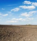 schwarzes Landwirtschaftsfeld und -wolken im blauen Himmel Stockfotos