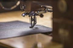 Schwarzes ledernes Stück genäht auf einer Handelsnähmaschine lizenzfreies stockbild