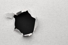 Schwarzes Loch im Papier Stockfotografie