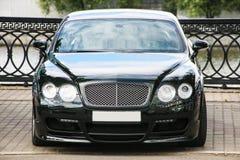 Schwarzes Luxusauto geparkt auf dem Damm Lizenzfreie Stockbilder