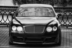 Schwarzes Luxusauto geparkt auf dem Damm Stockfotografie