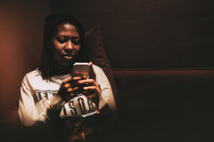 Schwarzes Mädchen, das Smartphone im dunklen Café, Nachtzeit verwendet lizenzfreies stockbild
