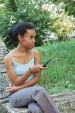 Schwarzes Mädchen mit Handy Lizenzfreie Stockfotos