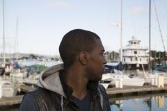 Schwarzes männliches Modell, das Boote auf den Jachthafen betrachtet Stockbilder