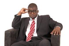 Schwarzes männliches vorbildliches Erwägen, während das Sitzen der Stuhl ist, der einen Anzug trägt Stockfotografie