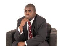 Schwarzes männliches vorbildliches Erwägen, während das Sitzen der Stuhl ist, der einen Anzug trägt Stockbild