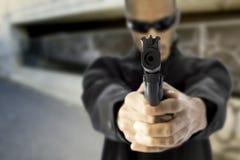 Schwarzes männliches Zeigegewehr am Zuschauer lizenzfreie stockbilder