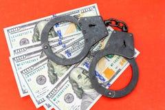 Schwarzes Metall fesselt das Lügen auf den 100 Dollar Banknoten auf einem roten Hintergrund mit Handschellen Stockbild