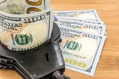 Schwarzes Metall fesselt das Lügen auf den 100 Dollar Banknoten mit Handschellen Stockbilder