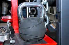 Schwarzes Metallgewicht 20 Kilogramm auf einem roten Metallgestell Lizenzfreies Stockfoto
